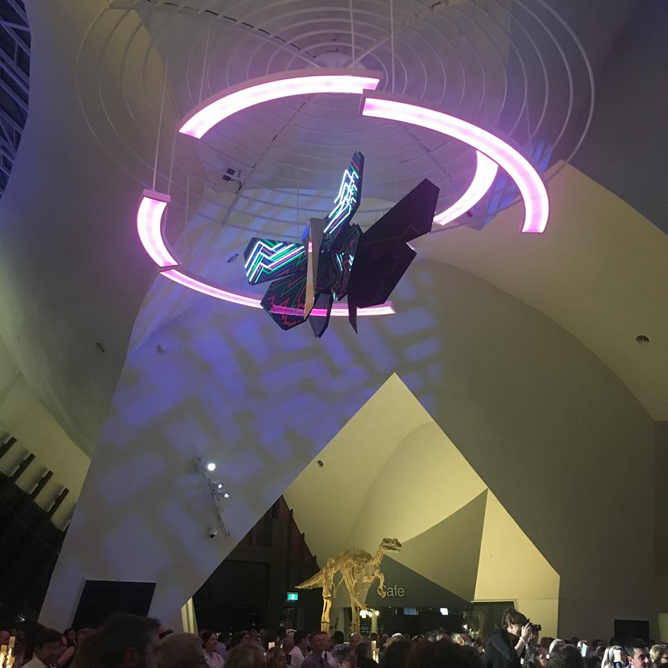 A butterfly shaped light above dinosaur bones and people sitting at tables having dinner